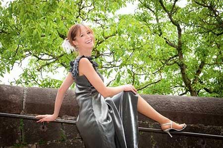 donna seduta su un albero con un vestito grigio
